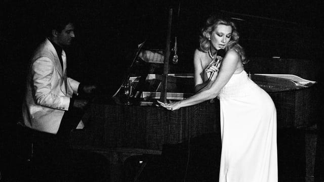 Eine Frau im langen weissen Kleid steht singend neben einem schwarzen Flügel.