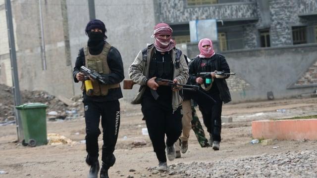 Symbolbild: Vier vermummte und bewaffnete Männer in einer Strasse im Irak.
