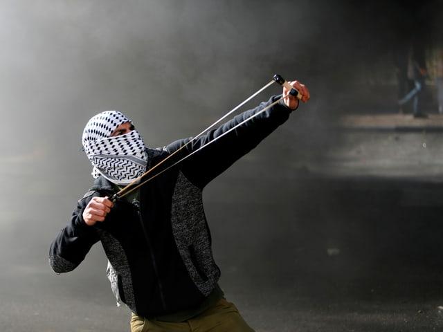 Ein palästinensischer Demonstrant schleudert Steine auf israelische Truppen.