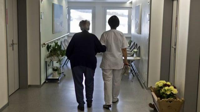 Eine betagte Frau wird von einer Pflegerin durch den Gang geführt.