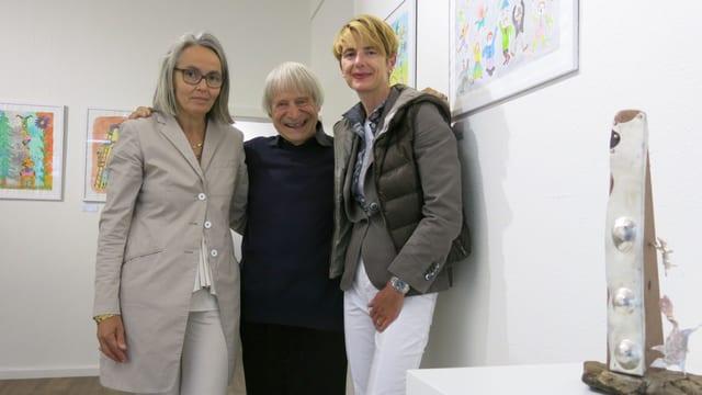 Michaela Grunder, Susanne Perren und Dimitri vor den bunten Bildern des Künstlers.