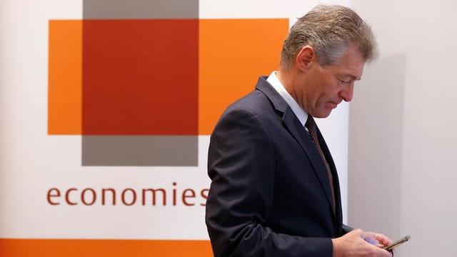 Heinz Karrer, il president d'Economiesuisse guarda sin ses telefonin.
