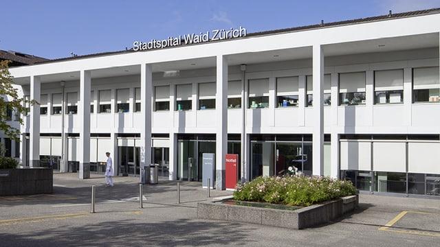 """Ein rechteckiges Gebäude von aussen, auf dem Dach prangt der Schriftzug Stadtspital Waid Zürich""""."""