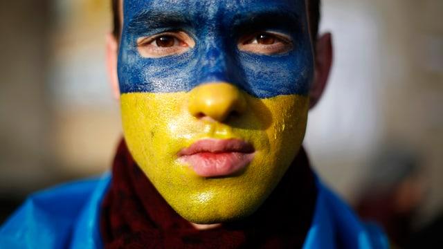 Ein Mann mit einer Ukraine-Flagge im Gesicht.