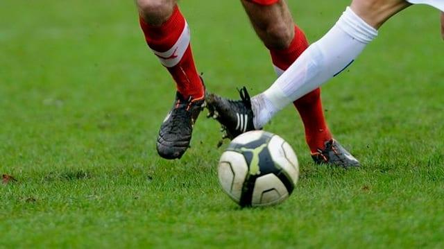 Szene aus einem Fussballspiel, bei dem die Beine zweier Spieler zu sehen sind die um einen Ball kämpfen.