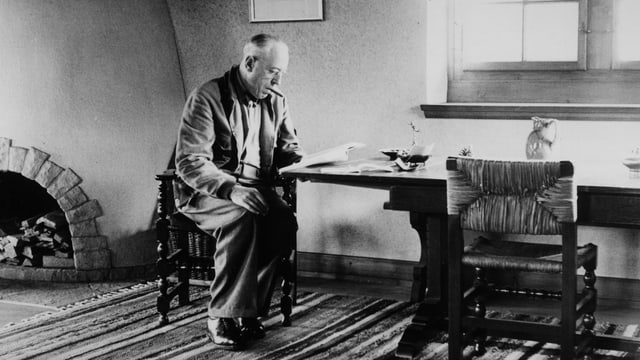 Albert Bächtold, mit Zigarre im Mund an einem Tisch sitzend, ein Buch lesend.