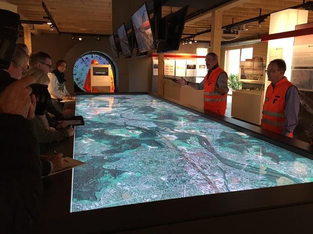 Menschen stehen um einen Tisch herum. Dessen Tischplatte ist eine leuchtende Landkarte des Baugebiets.
