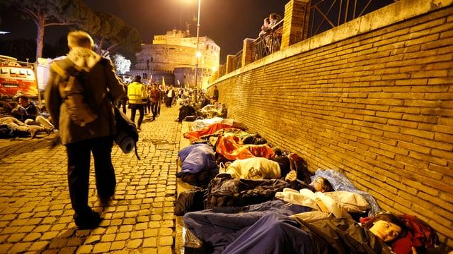 Menschen in Schlafsäcken auf einer Strasse