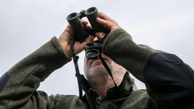 Jäger blickt mit dem Fernglas in die Ferne.