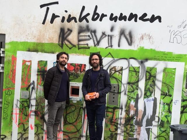 Zwei Männer mit schwarzen Haaren stehen vor einer Mauer. Darin hat es eine Öffnung. Die Wand ist komplett versprayt. Am oberen Rand des Bildes steht: «Trinkbrunnen».