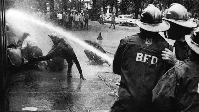 Feuerwehrleute richten den Wasserschlauch auf Demonstrierende.