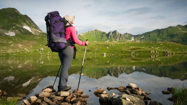 Wanderin mit Rucksack vor einem Bergpanorama.