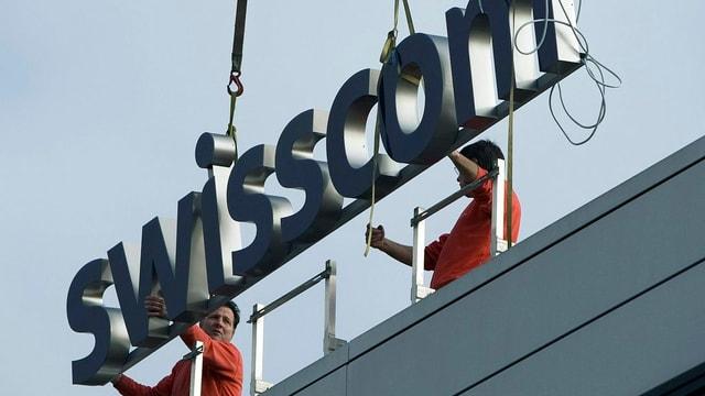Arbeiter montieren einen Swisscom-Schriftzug