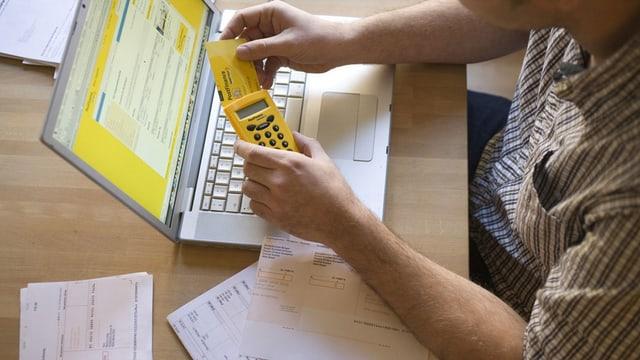 Mann am Laptop mit Postfinance-Seite offen.