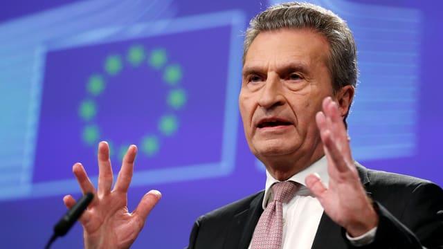 Oettinger spricht am Mikrofon mit erhobenen Händen und gespreizten Fingern vor der EU-Flagge.
