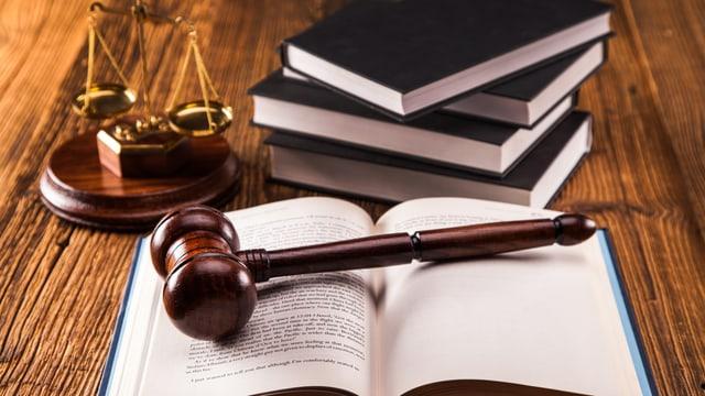 Gerichtsutensilien, Hammer und Bücher auf Tisch.