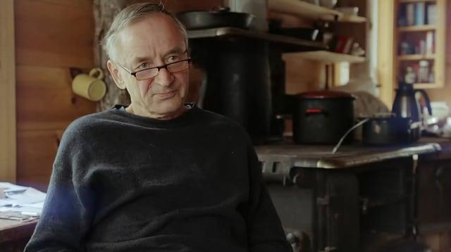 Ein Mann mit Brille und kurzen, grauen Haaren sitzt in seinem Häuschen.