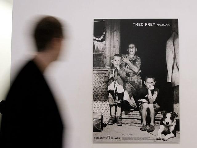 Ein Mann in einer Ausstellung geht an einem Foto vorbei, das eine Frau mit zwei Kindern zeigt.