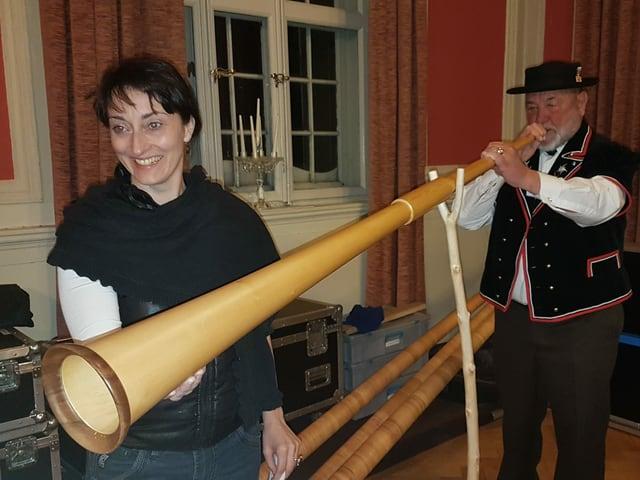 Ein Alphornspieler und eine Frau, die das Alphorn trägt.