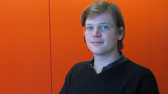 Junger Mann mit Brille vor roter Wand