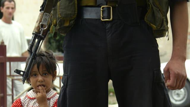Nahhaufnahme eines tschetschenischen Soldaten (Hüfthöhe) mit Gewehr, neben ihm steht ein Mädchen.
