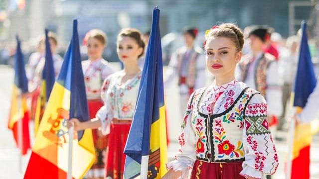 dunnas giuvnas da la Moldavia tegnan en maun la bandiera naziunala