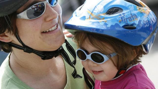 Kleines Mädchen mit Sonnenbrille und Velohelm.