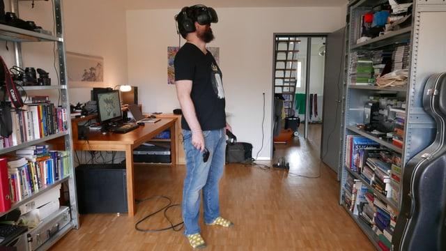 Eine Person steht in einem Wohnzimmer, trägt eine VR-Brille und hält Controller in der Hand.