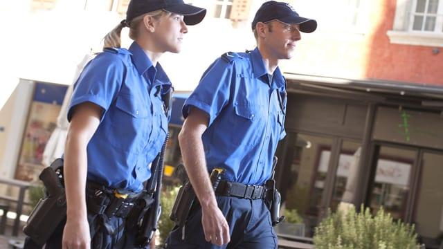 Eine Polizistin und ein Polizist auf Patrouille in einer Altstadt-Gasse