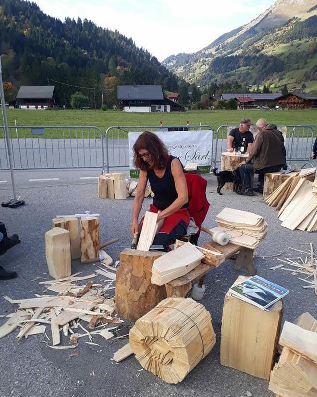 Eine Frau sitzt an einem Holzblock und schlägt Holzschindeln zurecht, bewaldete Voralpen im Hintergrund