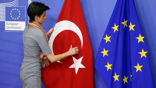 Eine Frau richtet die türkische Fahne, die neben einer EU-Fahne steht.