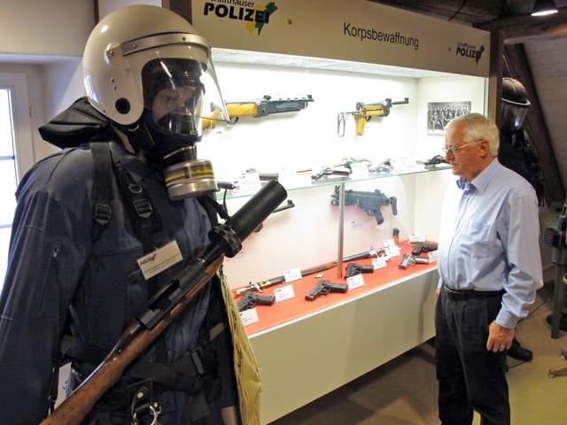Ex-Polizist Rolf Tuchschmid  vor der Vitrine der Polizebewaffnung.