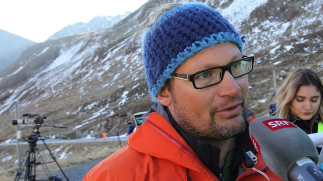 Ein Mann mit einer Strickmütze und orangen Gore-Tex-Jacke steht vor dem Mikrofon.