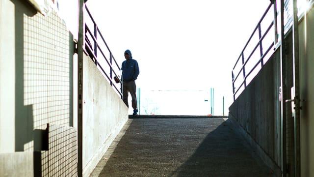 Ein Mann steht oberhalb einer Rampe, die aus einem Unterirdschen Raum herausführt.