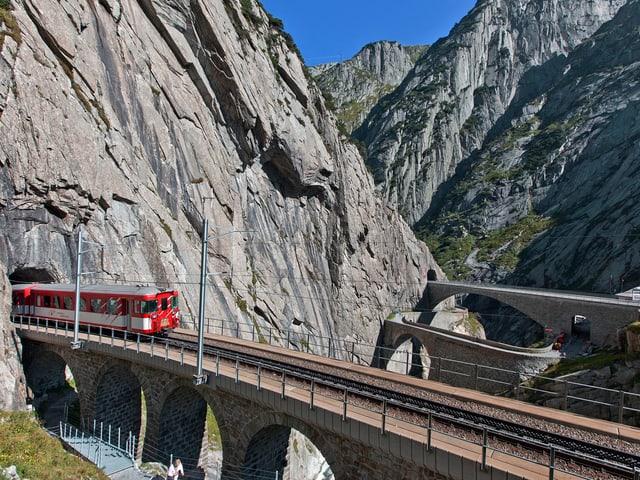 Die Bahn auf dem Weg durch die Schöllenenschlucht entlang der alten Teufelsbrücke im Kanton Uri.