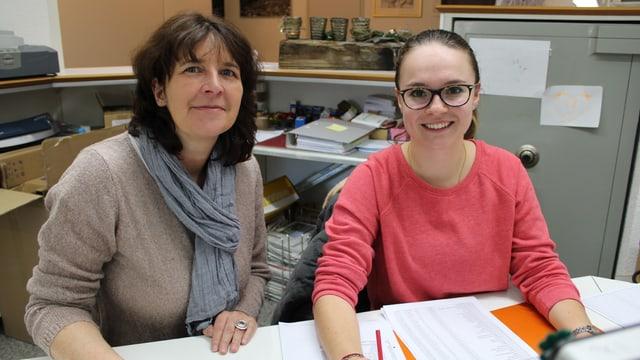 Patrizia Burgener und Lisa Codalonga sitzen an einem Bürotisch.