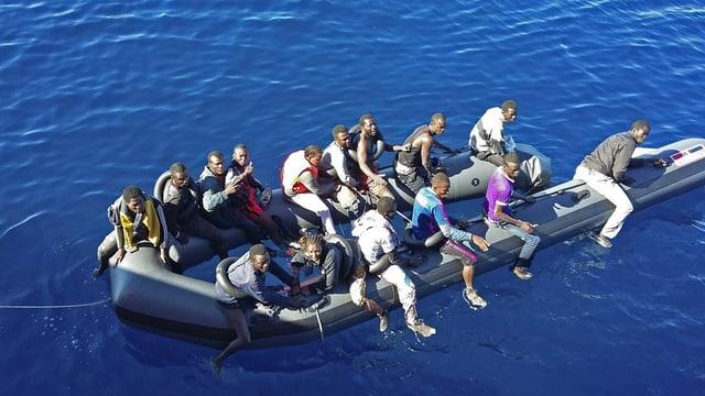 Symbolbild: 15 Afrikaner auf einem offenbar langsam sinkenden Gummiboot auf dem Meer.