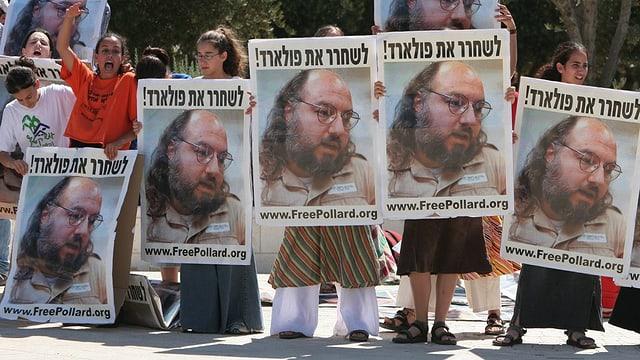 Demonstranten halten Plakate mit einem Bild von Pollard.
