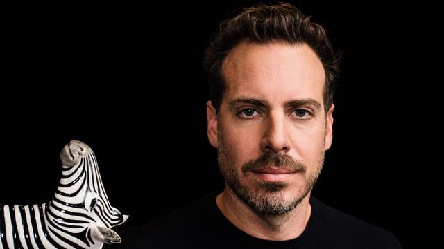 Porträtbild von Tom Gisler. Vorne links ist auch ein kleines Holzzebra zu sehen.