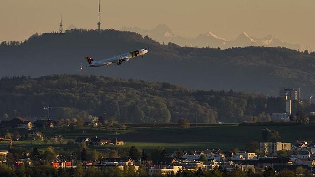 Flugzeug über Häuser und Wald
