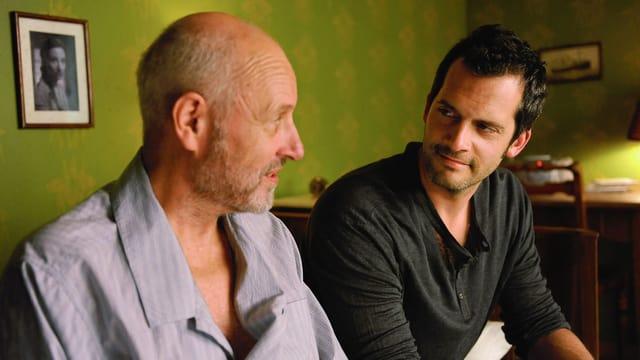 Ein älterer Mann mit halboffenem Hemd, neben im sitzt ein jüngerer Mann, sie sehen sich vertraut an.