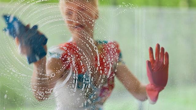 Eine Frau putzt eine Scheibe