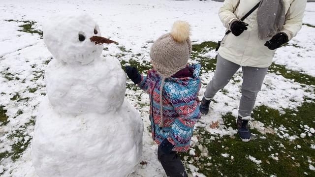 Ein Kind baut einen Schneemann, eine erwachsene Person steht daneben, von der man nur die Beine sieht.