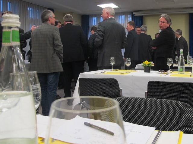 Im Vordergrund Flasche und Glas - im Hintergrund diverse Männer beim Gespräch.