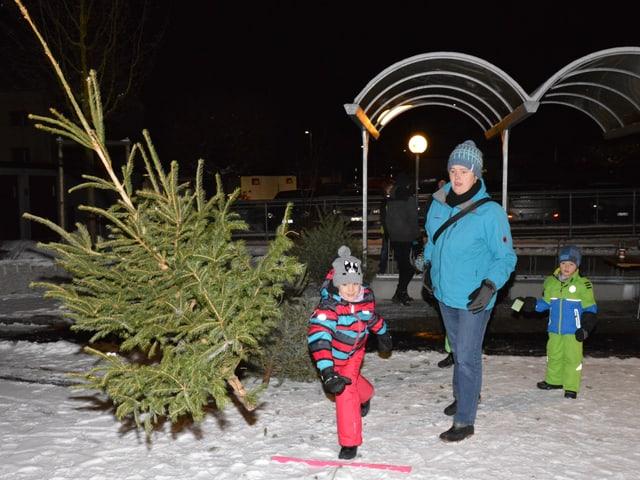 Kind wirft Christbaum. Frau steht daneben.