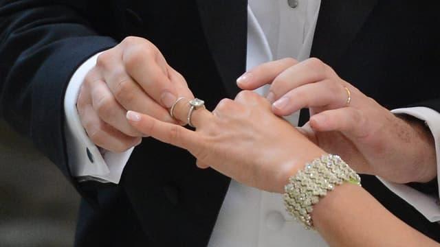Mann zieht Frau Ehering an