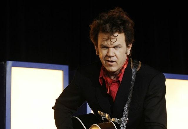 Ein Mann mit einer Gitarre singt.