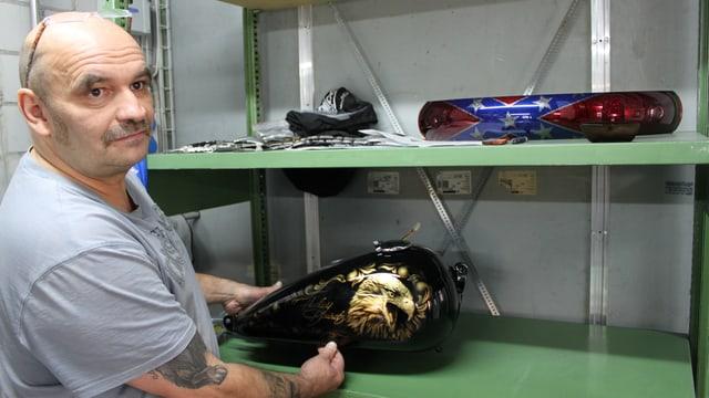 Mann aus der Harley-Werkstatt zeigt, was er gemacht hat. Ein Teil eines Töffs ist zu sehen.