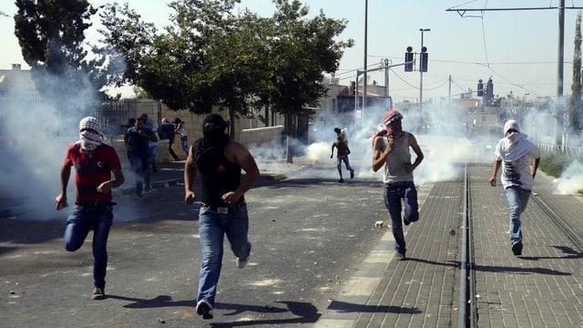 Junge Menschen rennen auf einer Strasse.