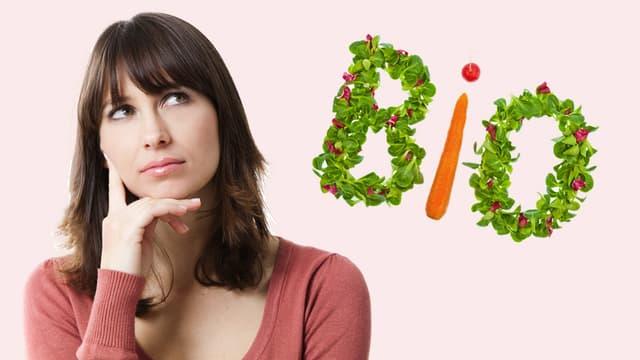 Eine Frau schaut nachdenklich auf ein Bio-Logo.